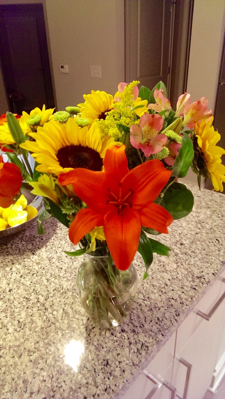Sunflowers, orange birds of paradise Trader Joe's flowers on granite countertops