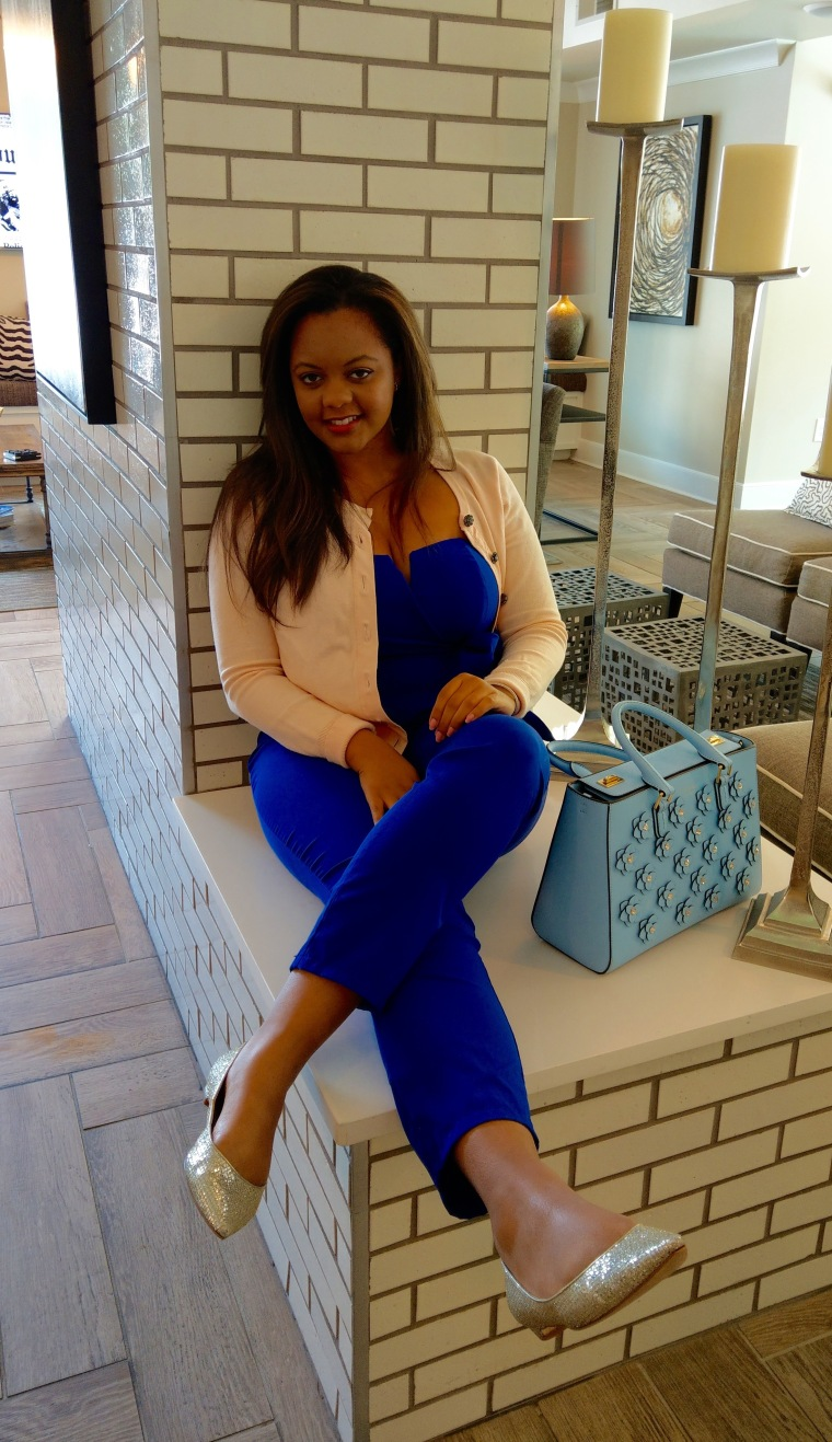 Pastel pink cardigan, cobalt blue jumpsuit, silver shoes on Keri Elaine with a Henri Bendel bag