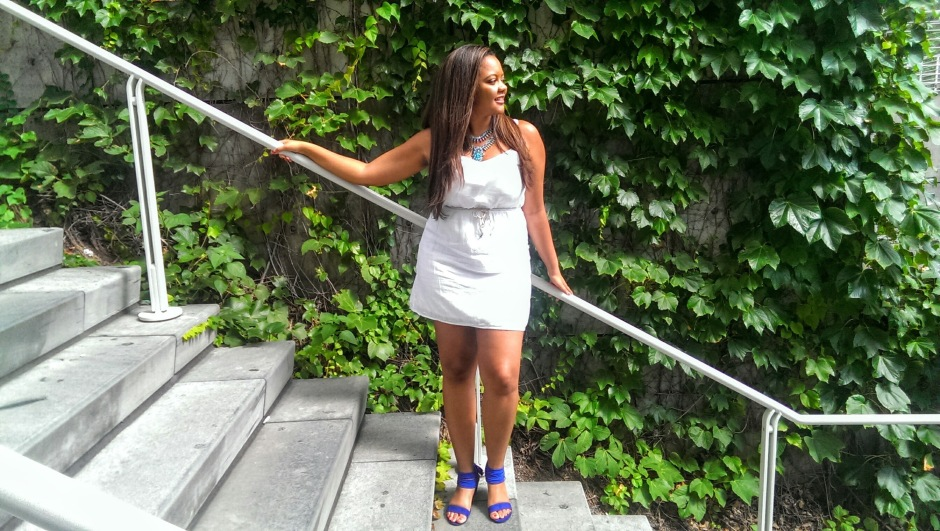 Beautiful black girl with a white dress on and cobalt blue shoes, on stairs with ivy at the High Museum of Art in Atlanta